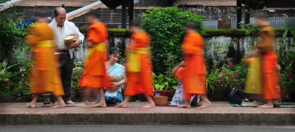 Monks process at dawn through the town of Luang Prabang, Laos, begging alms in a daily ritual that has become a major tourist spectacle.