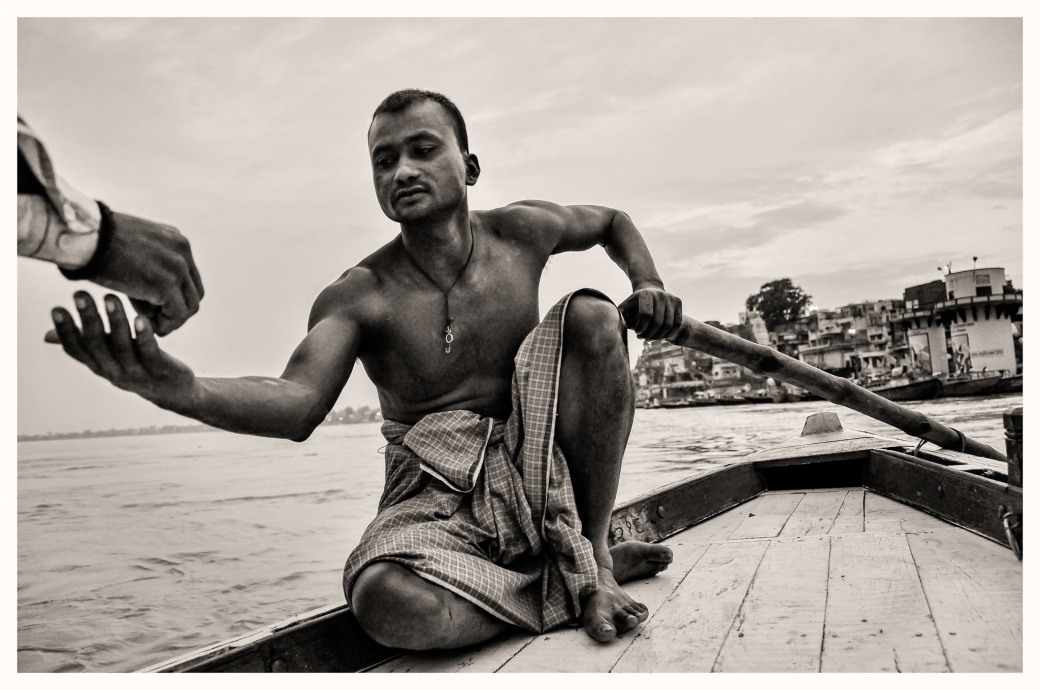 A boatman reaches for a handful of tobacco on the Ganges at dawn.